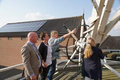 Gedeputeerde Hester May, wethouder Liesbeth Grijsen en Meester molenaar Tonnie Moes lichten de vang onder toeziend oog van Pieter van der Vinne. (Foto: Jaques Bakker.)